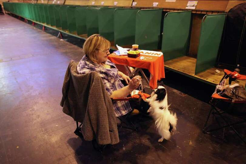 BIRMINGHAM, ENGLAND - MARCH 13:  A woman rests with her Papillon dog at the end of the final day of