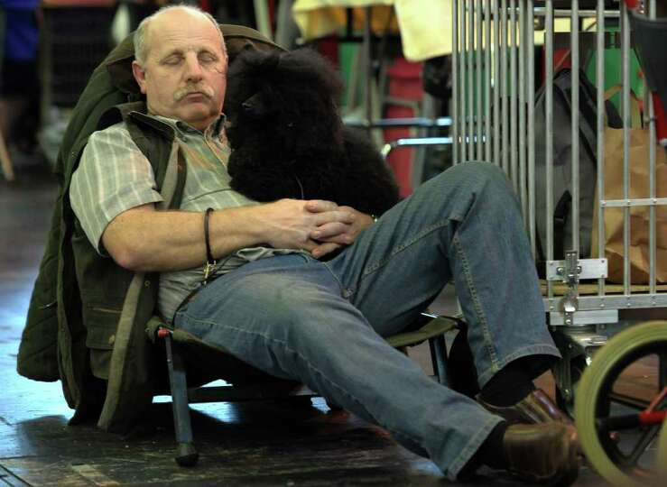 A man rests with a dog on the final day of the annual Crufts dog show at the National Exhibition Cen