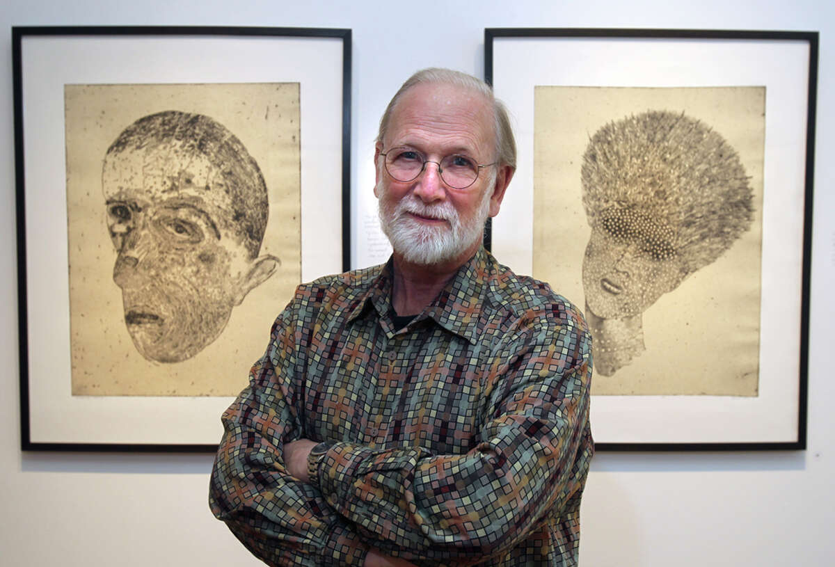 Artist Dennis Olsen stands in front of two of his creations at the REM Gallery on Park Avenue.