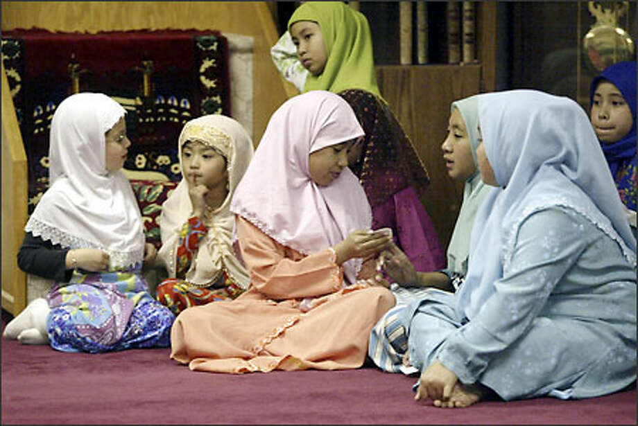Muslim girls compare numbers drawn in a Quran reading competition at the mosque in Cham community in Lacey. Photo: Jim Bryant/Seattle Post-Intelligencer