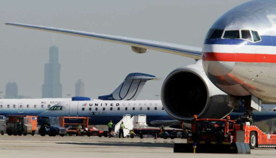 In this photo taken Oct. 5, 2010, an American Airlines jet, right, taxis past United Airlines and United Express jets at O'Hare International Airport in Chicago as the Willis Tower looms in the background. On Monday, March 14, 2011, officials with the U.S. Department of Transportation say there's a partial agreement in a long-running dispute between the city of Chicago and both United and American airlines over further expansion of O'Hare. (AP Photo/M. Spencer Green) Photo: M. Spencer Green
