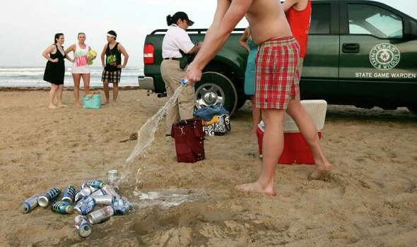 "An underage spring breaker pours out beer after being stopped by Texas Game Wardens Sunday March 13, 2011 during ""Texas Week"" on South Padre Island. Photo: EDWARD A. ORNELAS, Express-News / SAN ANTONIO EXPRESS-NEWS NFS"