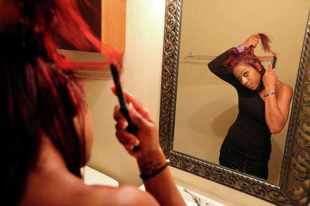"University of Central Oklahoma student Porsha Riley, 20, styles her hair before going out Sunday March 13, 2011 during ""Texas Week"" on South Padre Island. Photo: EDWARD A. ORNELAS, Express-News / SAN ANTONIO EXPRESS-NEWS NFS"