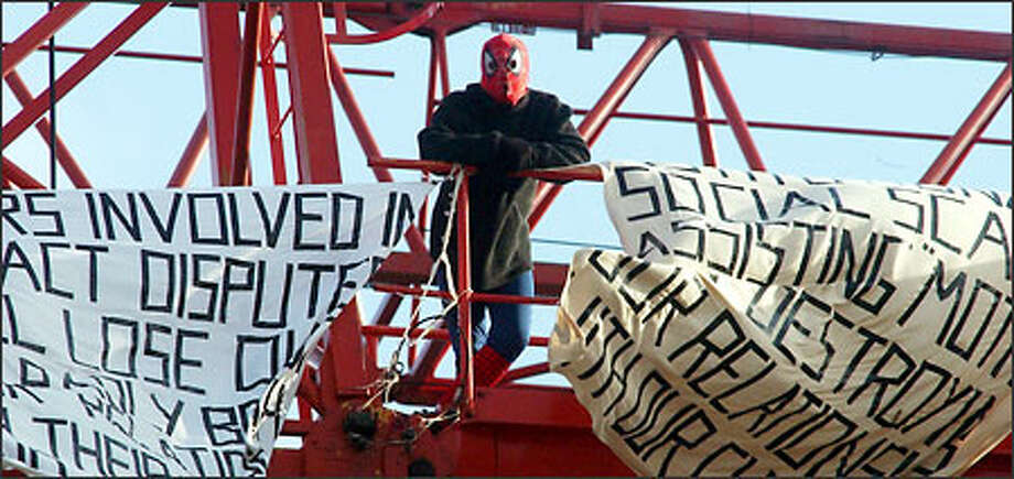 David Chick, dressed as Spider-Man, stands among his banners during his sit-in protest up a crane in the shadow of London's Tower Bridge yesterday. Photo: AP