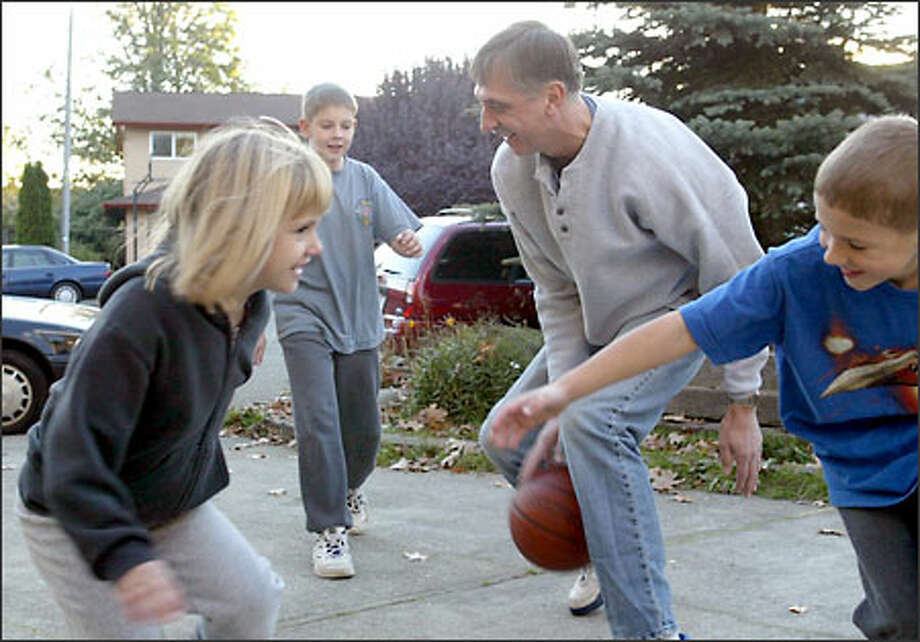 Rod Derline dribbles between his legs as he plays basketball with his children in the driveway of their Kent home. On defense, from left, are Joy, 6, Carl, 10, and Isaac, 8. Photo: Scott Eklund/Seattle Post-Intelligencer