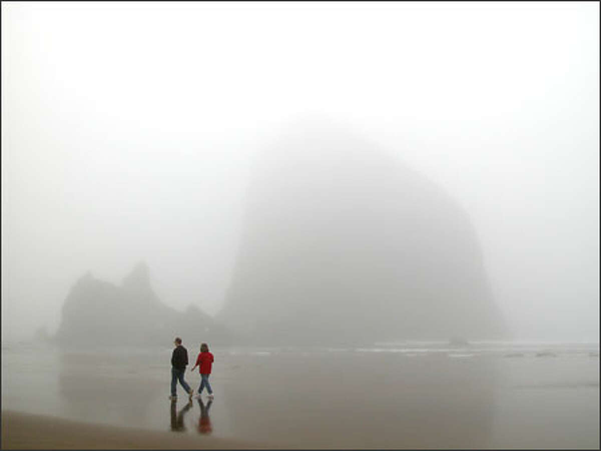Fog obscures Haystack Rock during a calm low tide. However, when the winds kick up, walking the beach can become dangerous.