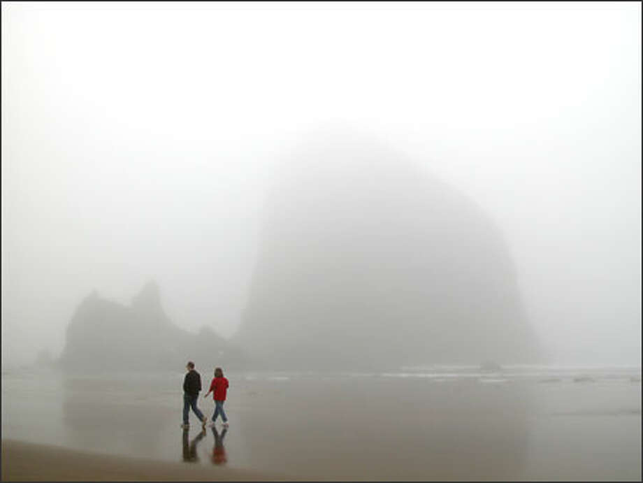 Fog obscures Haystack Rock during a calm low tide. However, when the winds kick up, walking the beach can become dangerous. Photo: / George Vetter