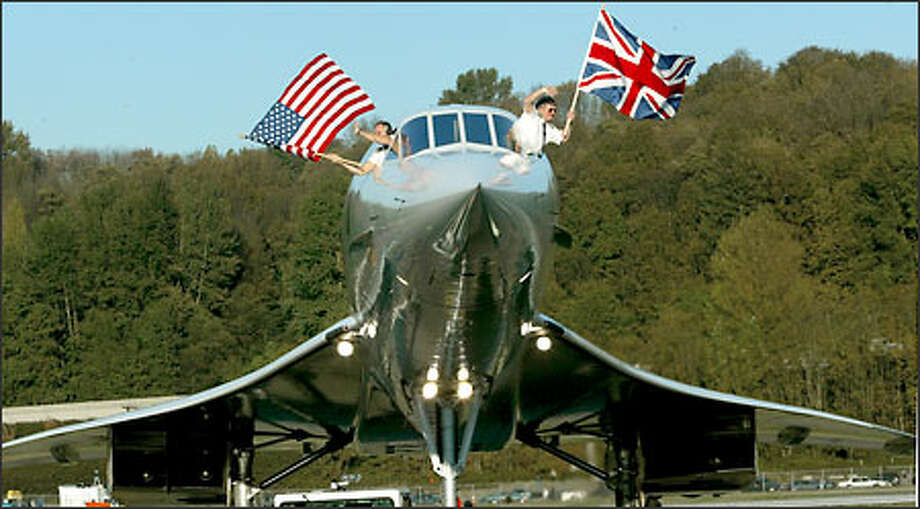 Concorde pilots Les Broadie, left, and Mike Bannister wave American and British flags from the plane as it is pulled into its parking place at the Museum of Flight. Photo: Grant M. Haller/Seattle Post-Intelligencer