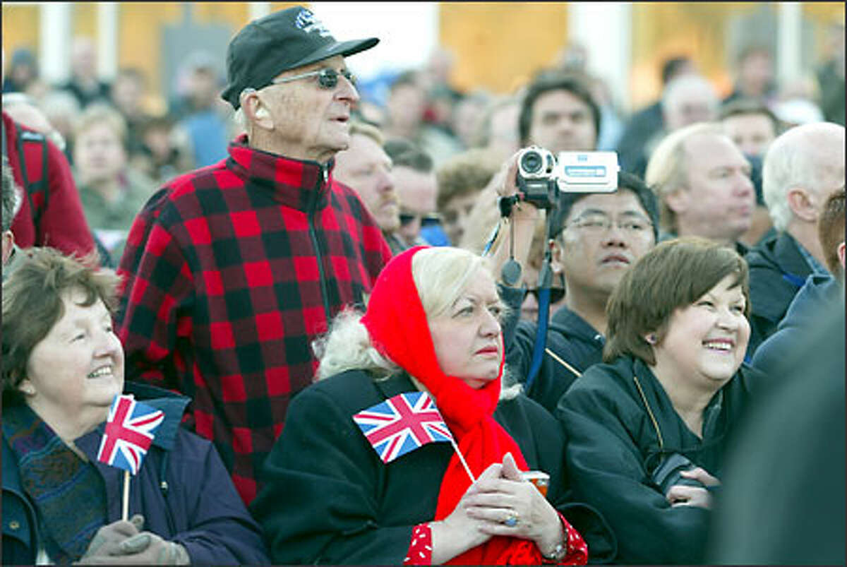 Among the thousands on hand to see the Concorde arrive yesterday were, from front left, Maureen Drabb and Judy Mason, both with flags, and Paula Clark; second row, Rolland Kruzz, in cap, and Jim Lee, holding camera.