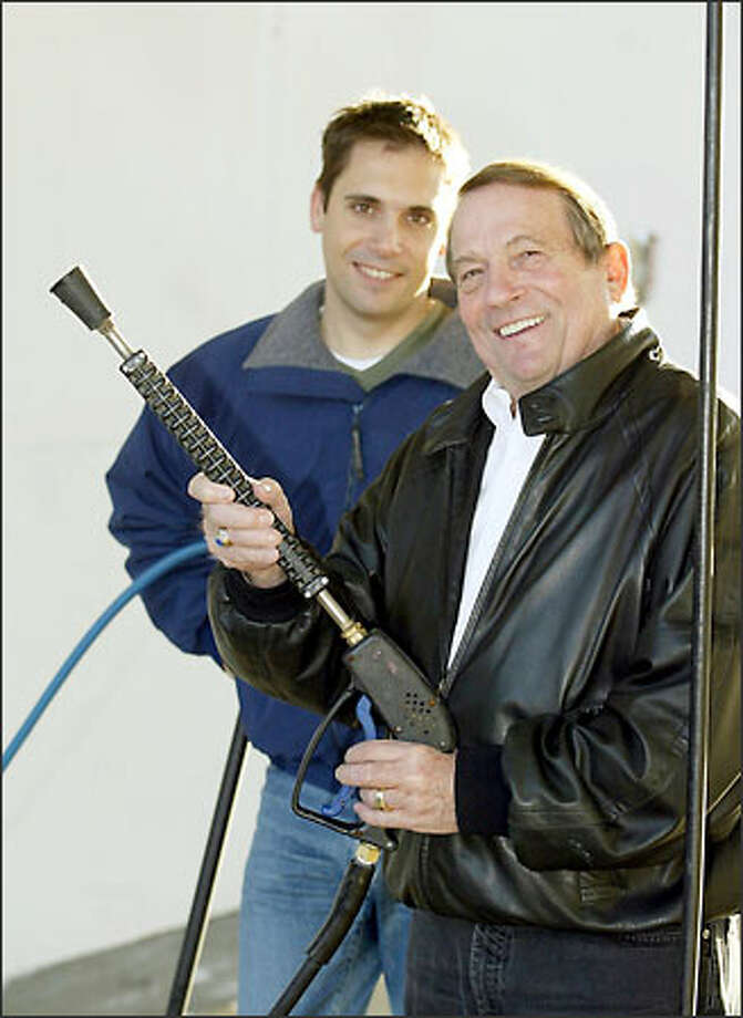 Vice President Lance Odermat, left, and his dad, founder and President Vic Odermat, of Car Wash Enterprises Inc., pose with car-cleaning equipment at a self-service Brown Bear car wash in Seattle yesterday Photo: Meryl Schenker/Seattle Post-Intelligencer
