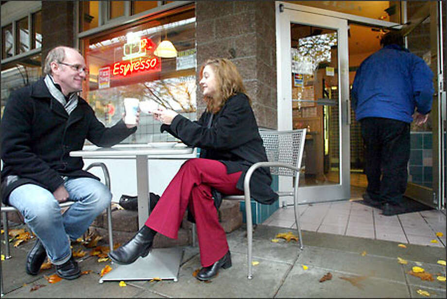 """At a Fifth Avenue cafe, Carl Rohde, known as """"Dr. Cool,"""" and Lisa Revelle, a """"cool hunter"""" with Rockey Hill & Knowlton, toast their effort on a """"cool list,"""" which identifies cool spots and trends in the city. Photo: Joshua Trujillo/Seattle Post-Intelligencer"""