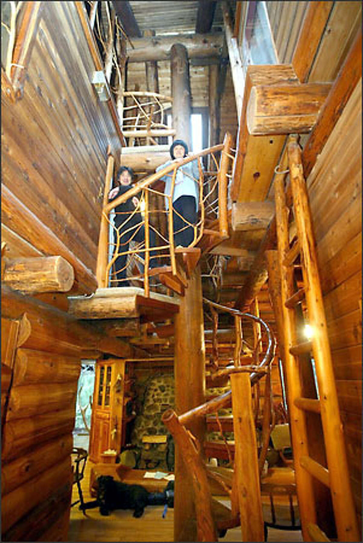 Chiaki Takanohara, left, and Kyoko Niikuni stand on one of the landings of the spiral staircase in their log house they built near Carnation. They began building in 1983, one log at a time, and moved into their creation in 1985.