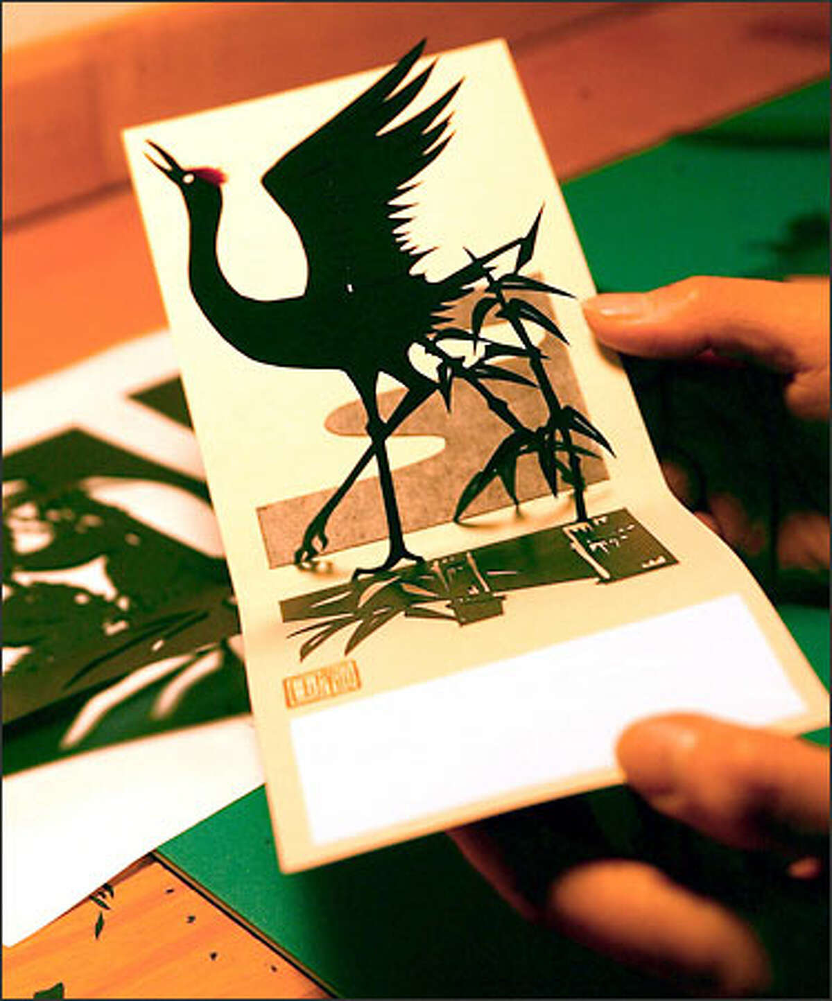 Paper artist Kyoko Niikuni opens one of her folding cards to show the crane inside. She makes Japanese torn- and cut-paper creations.