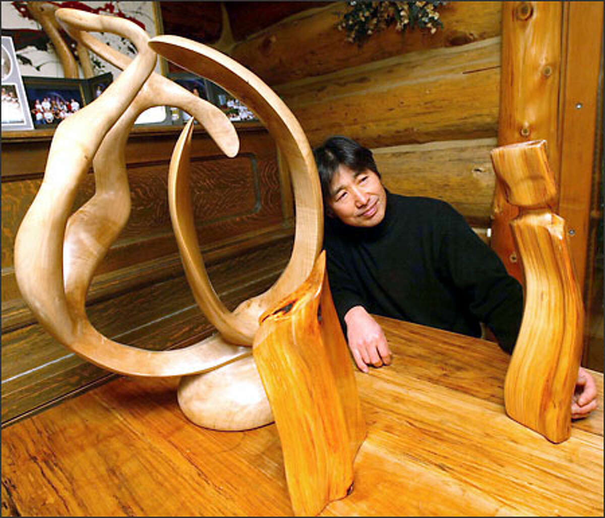 Chiaki Takanohara looks over some of his pieces. His work with wood goes beyond creating his home to smooth wood carvings.