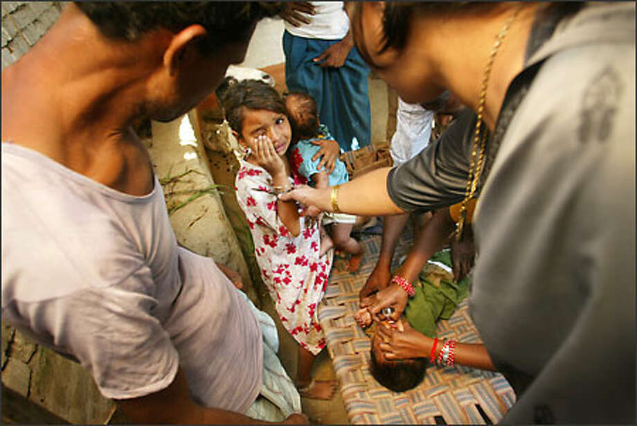 Health workers descend upon a home in a north India village while all the adults are out and begin vaccinating the children. Photo: Mike Urban/Seattle Post-Intelligencer