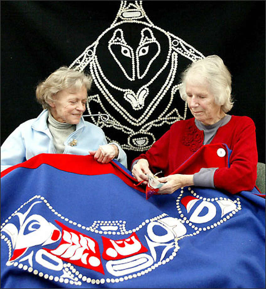 Mary Woodruff, left, and Catherine Troeh with a handmade blanket that Troeh gave Woodruff before leaving the Foss Home, where the two women met. Photo: Meryl Schenker/Seattle Post-Intelligencer