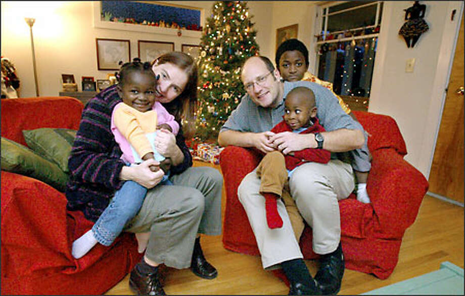 Majken Ryherd, Michael James and 7-year-old son Sana, rear, will share Christmas in their Wallingford home with newly adopted Adama Kay, 2, left, and Bassie Leigh, 4. Daughter Adama and son Bassie are recent arrivals from Sierra Leone, where each was orphaned by the nation's civil war. Ryherd and James adopted Sana from Guinea six years ago. Photo: Gilbert W. Arias/Seattle Post-Intelligencer