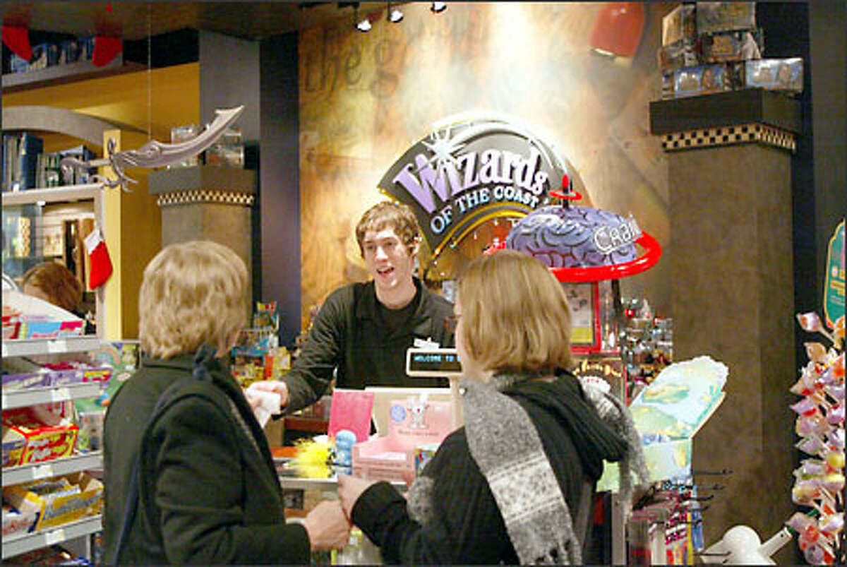 Sarah Rhamey, left, and daughter Becky Rhamey are served by Travis Burkett at Wizards of the Coast at Northgate Mall. The store chain is closing