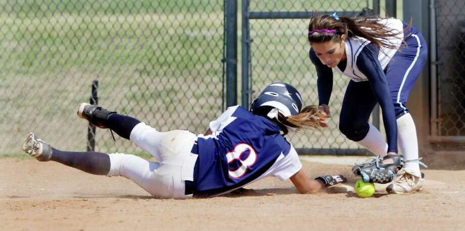Roosevelt's Sharlene Castro dives back to first as Johnson's Cosette Hernandez can't make the tag on a pickoff attempt. The Jaguars scored their two runs Monday without a hit. BOB OWEN/rowen@express-news.net Photo: BOB OWEN, SAN ANTONIO EXPRESS-NEWS / SAN ANTONIO EXPRESS-NEWS