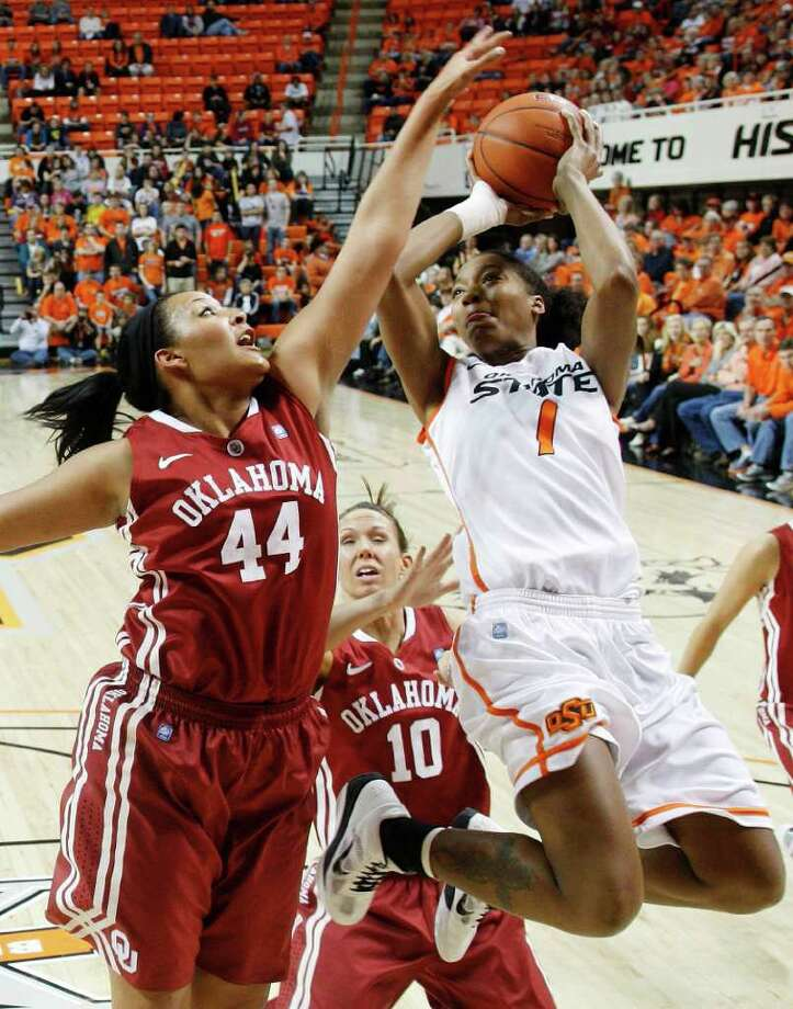 Oklahoma forward Lyndsey Cloman (left) defends as Oklahoma State guard Precious Robinson shoots on  Jan. 29, 2011. Photo: AP