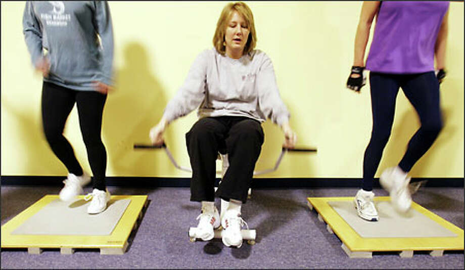 """Meg Wakeman, bottom center, who has been exercising at the facility for about seven months, says, """"I've really noticed the muscle tone."""" Photo: Mike Urban/Seattle Post-Intelligencer"""
