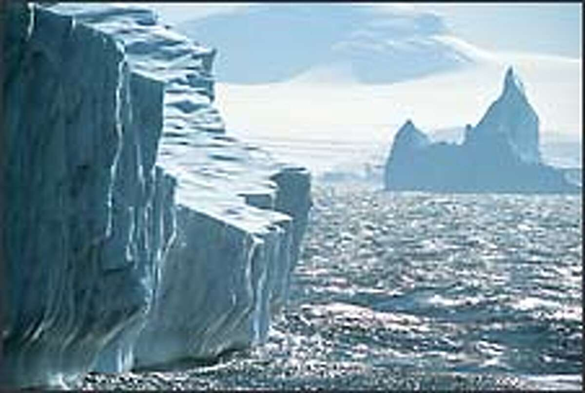 Like floating castles, a pair of icebergs stand watch over Adelaide Island in Crystal Sound.
