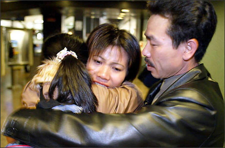 Ba Bui embraces his wife, Hoai Nguyen, and their daughter, Hang Bui, at Sea-Tac Airport. Nguyen's family was given a special visa to come here. Photo: Meryl Schenker/Seattle Post-Intelligencer