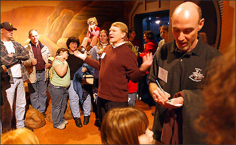 """Brian Muirhead, chief engineer at the Mars Science Laboratory, right, signs autographs at the Pacific Science Center yesterday as former astronaut George """"Pinky"""" Nelson talks with visitors. Photo: Jeff Larsen/Seattle Post-Intelligencer"""