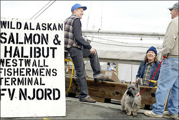 Mark Johansen, left, and Pete Knutson, center, talk with Mark's father, Gary Johansen, shown with his dog, Bart, at the West Wall at Fishermen's Terminal. The fishermen are selling salmon, halibut and prawns to the public, which they caught and froze at sea off Alaska. Photo: Karen Ducey/Seattle Post-Intelligencer