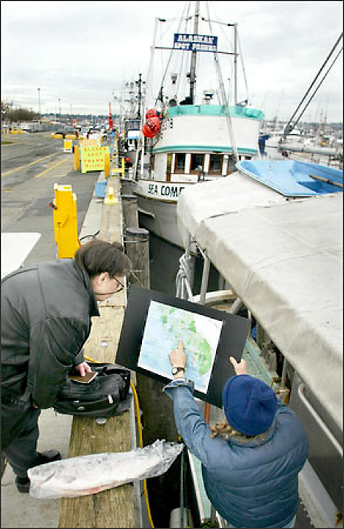 Pete Knutson shows Dee Salvino, left, the fishing grounds he harvested.