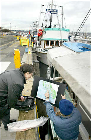Pete Knutson shows Dee Salvino, left, the fishing grounds he harvested. Photo: Karen Ducey/Seattle Post-Intelligencer