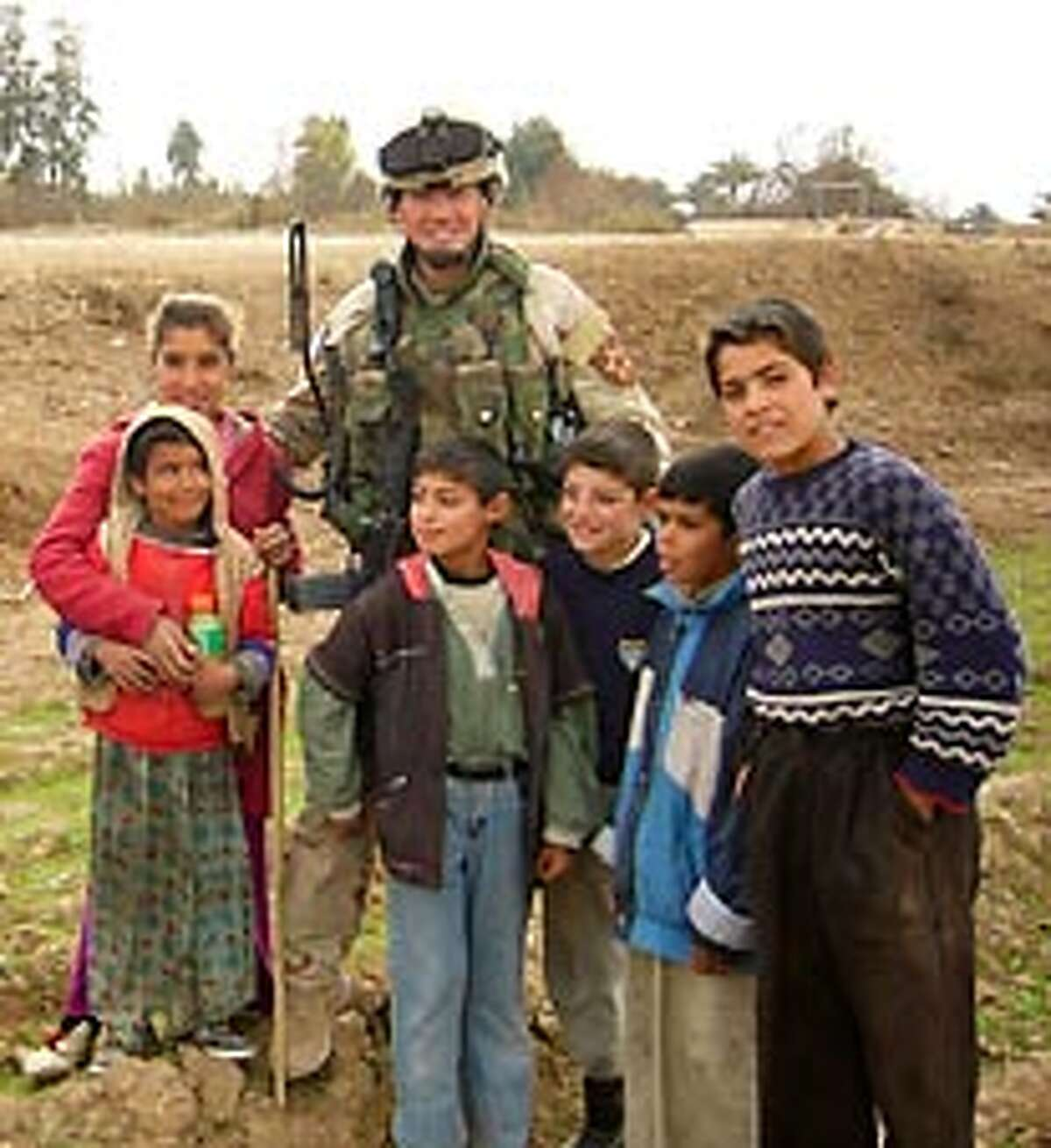 Christopher Bunda is shown in a recent photograph standing with children in Iraq. Bunda sent the photo to his wife and kids back home.
