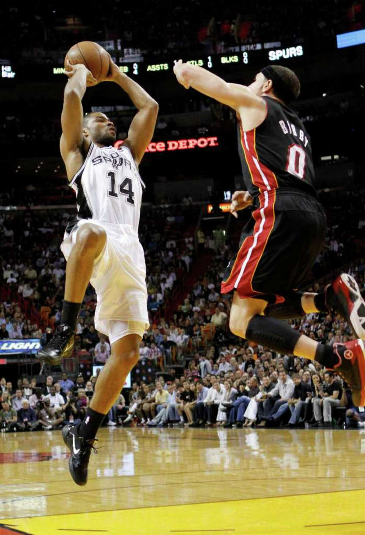 San Antonio Spurs' Gary Neal (14) prepares to shoot over Miami Heat's Mike Bibby (0) in the second quarter of an NBA basketball game in Miami, Monday, March 14, 2011. The Heat won 110-80.