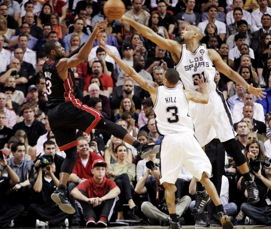 Miami Heat's Dwyane Wade (3) shoots over San Antonio Spurs' Tim Duncan (21) and George Hill (3) in the second quarter of an NBA basketball game in Miami, Monday, March 14, 2011. Photo: AP