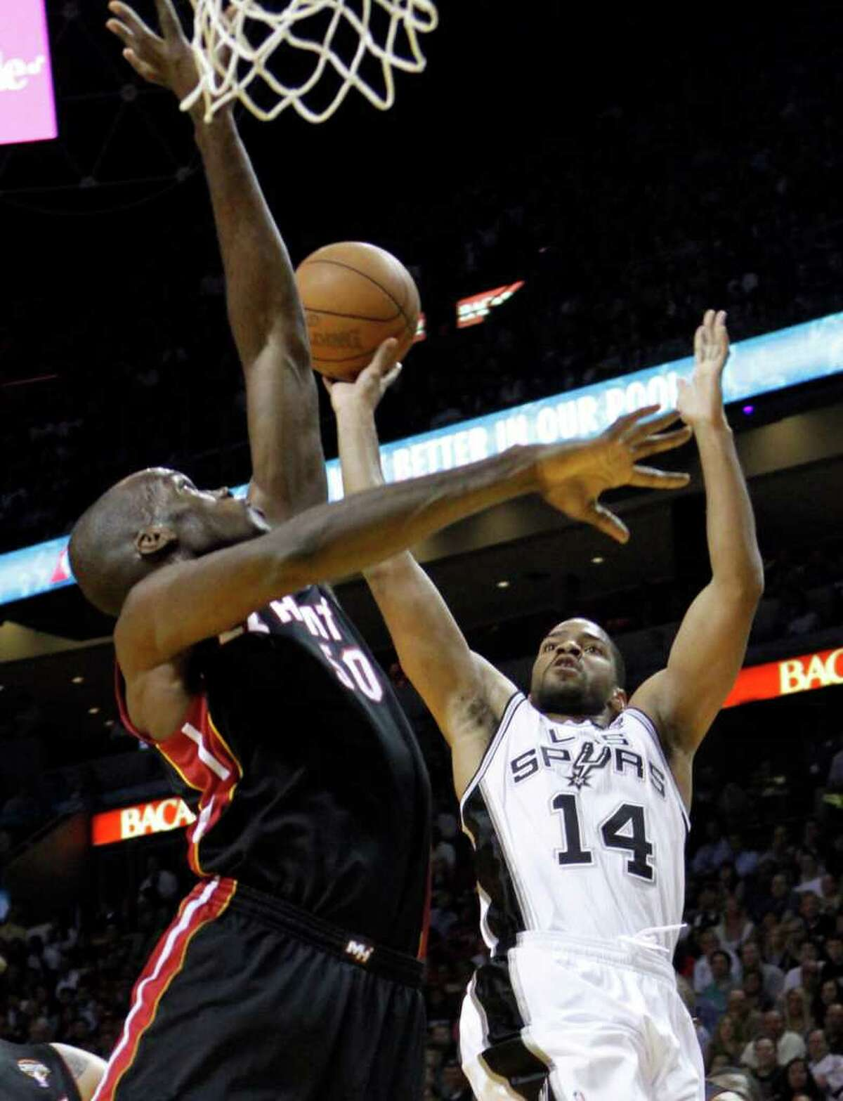 San Antonio Spurs' Gary Neal (14) prepares to shoot as Miami Heat's Joel Anthony (50) defends in the first quarter of an NBA basketball game in Miami, Monday, March 14, 2011.