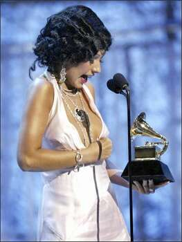 "Singer Christina Aguilera refers to the Janet Jackson Super Bowl incident as she adjusts her dress to cover her breast while accepting the award for best female pop vocal for ""Beautiful"" during the 46th Annual Grammy Awards. Photo: / Associated Press"