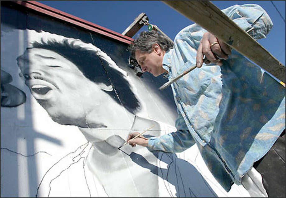 Seattle artist Don Rockwell works on a mural of rock icon Jimi Hendrix on the side of Tower Records on Mercer Street in Seattle. The project will consist of four of Hendrix's album covers and a concert scene. Photo: Gilbert W. Arias/Seattle Post-Intelligencer