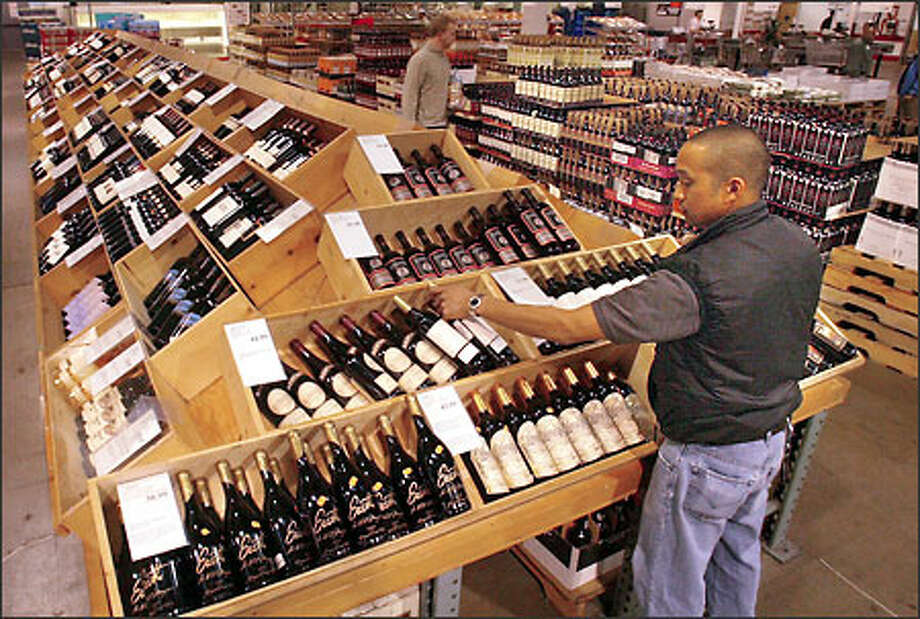 Fred Borja, a stocker, works in the wine section at the Costco store on Fourth Avenue South in Seattle yesterday. Under state regulations, retailers can't buy alcohol from manufacturers; instead, they must buy from distributors, who mark up prices by at least 10 percent. Photo: Phil H. Webber/Seattle Post-Intelligencer
