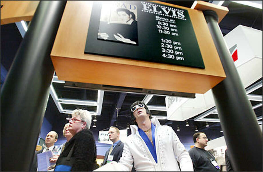 Elvis (aka John Monforto of Woodstown, N.J.) checks out his schedule at the Checkpoint booth in the Public Library Association's national convention in the Washington State Convention and Trade Center yesterday. Checkpoint Systems makes collection-management systems. Photo: Paul Joseph Brown/Seattle Post-Intelligencer