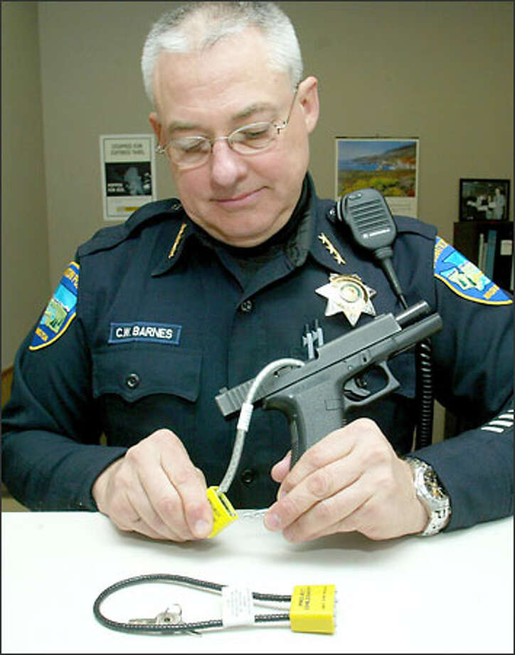 Carnation police Chief Craig Barnes demonstrates how a cable gun lock works on a semiautomatic pistol. The infusion of federal money will allow distribution of 20 million free locks nationwide, officials say. Photo: Grant M. Haller/Seattle Post-Intelligencer