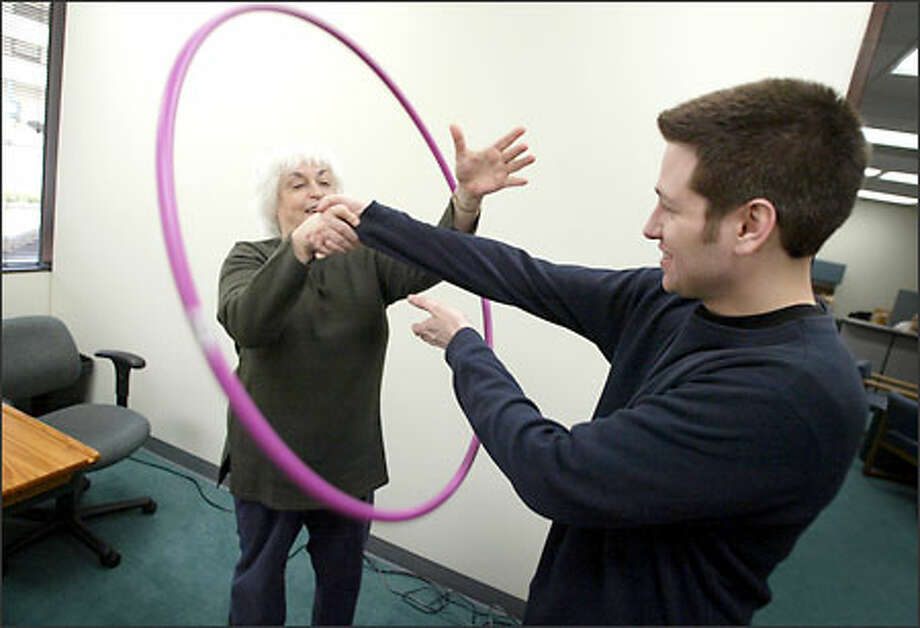 Judith Bluestone and program assistant John Carroll demonstrate an exercise designed to improve memory. Photo: Joshua Trujillo/Seattle Post-Intelligencer