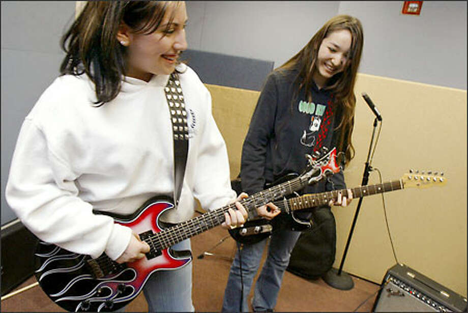 "Priscilla Christ, 14, left, and Liana Hirosaki, 15, both of Kirkland, rehearse for Rock School's ""Girls Rock Night"" at BEST High School in Kirkland. The name of their band is Dolly Done Good. Photo: Meryl Schenker/Seattle Post-Intelligencer"