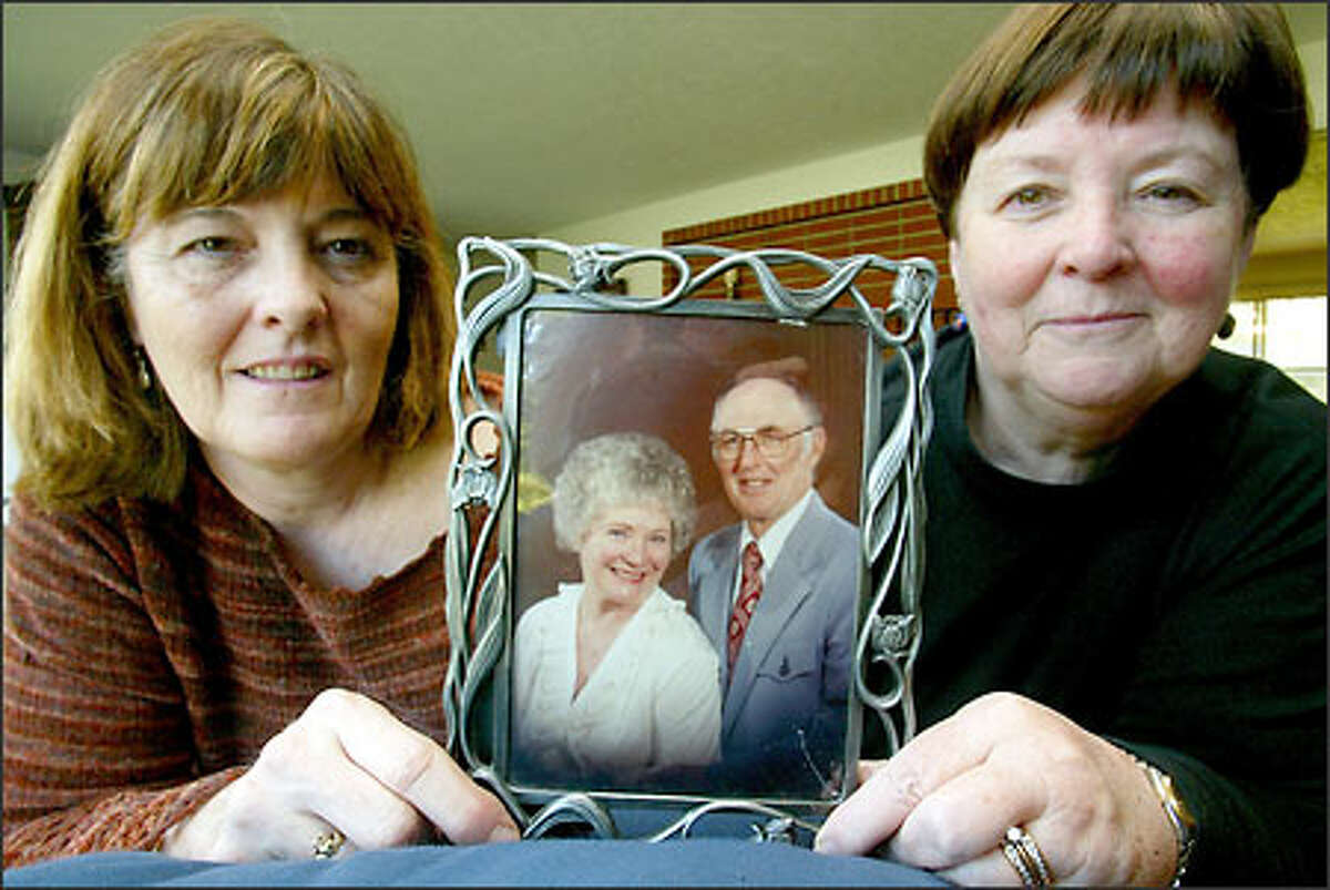 Sisters Patty Anderson, left, and Jeanne Giese hold a picture of their parents, Rose and Jim Henry. An autopsy that the family had done after Rose Henry's death in 1997 revealed that she died of a rare disorder called Creutzfeld-Jakob disease.
