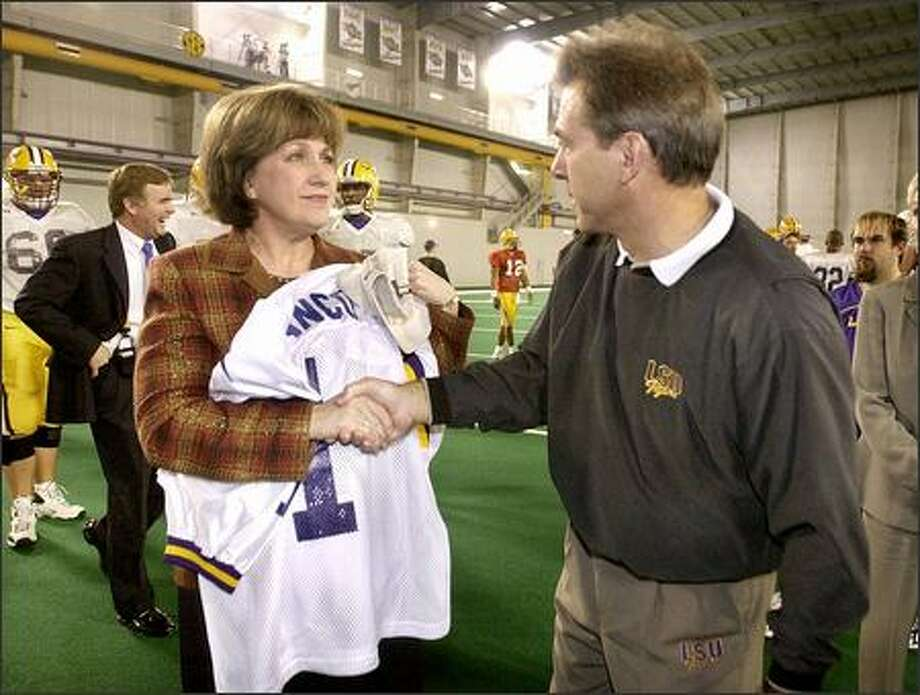 Mark Emmert, back left, stayed near LSU football and coach Nick Saban, giving a jersey to Gov. Kathleen Blanco. Photo: / Associated Press