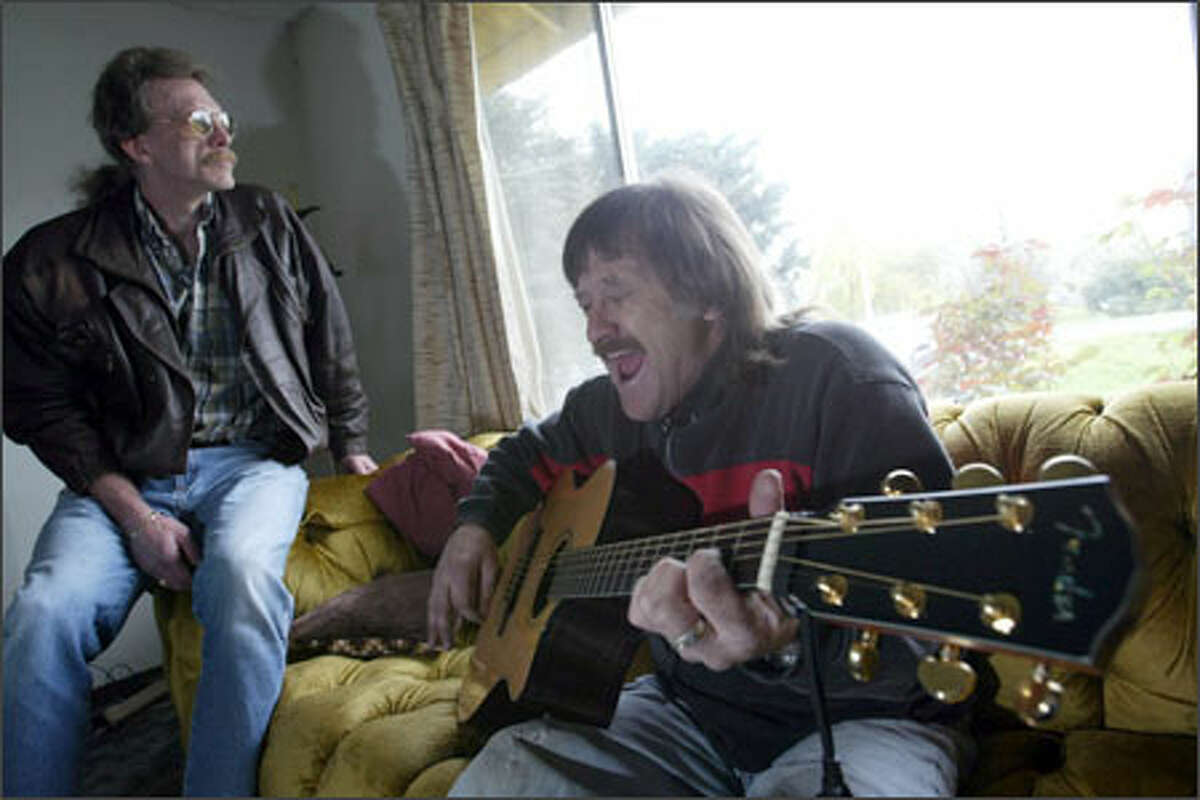 Dan Gleason, a resident of Hope House N.W., plays his guitar and sings in the group home in Pacific. At left is Tom Henning, president of Hope House.
