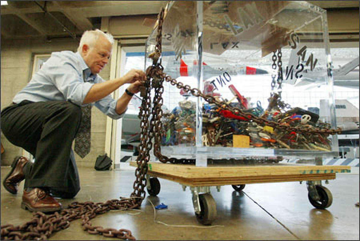 """Artist Steve Maloney prepares his """"Banned Booty"""" artwork for display starting today at the Museum of Flight. Maloney bought 270 pounds of items seized from travelers at airports with the idea of turning them into art. It features, among other things, Swiss Army knives, squirt guns and lighters."""