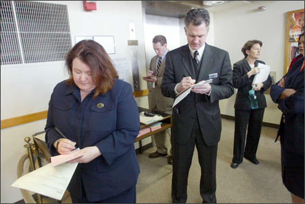 """Lobbyists, including Lonnie Johns-Brown, left, """"work the door"""" outside the state Senate in Olympia, writing notes to senators on legislation important to their causes. Johns-Brown is a self-employed """"contract lobbyist."""""""