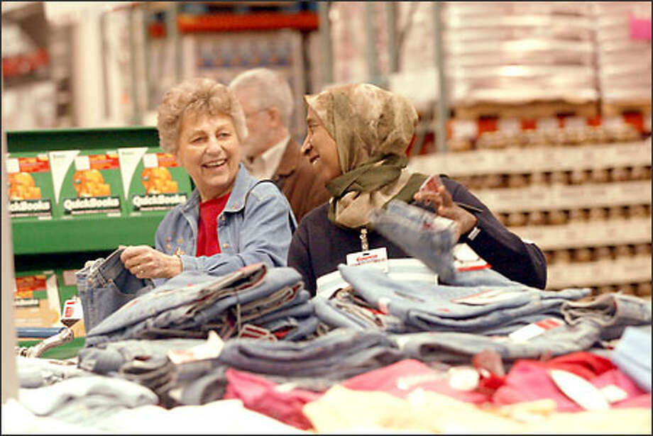 Mako Ahmed helps Marilyn Fetrow at the Aurora Village Costco store. Ahmed, a 5-year store veteran, says she enjoys going to work every day. Photo: Phil H. Webber/Seattle Post-Intelligencer