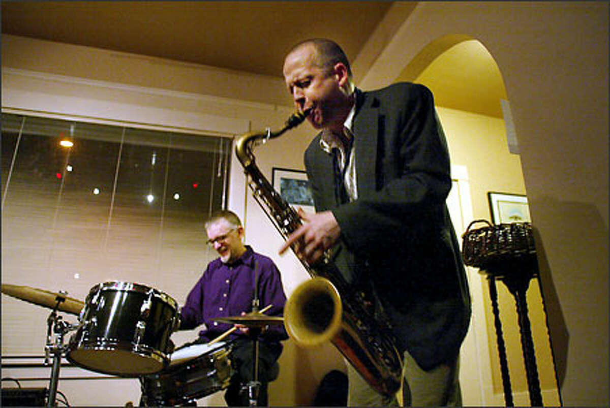 Tad Britton on drums and Hans Teuber on saxophone playing in the living room Mark and Barbara Hubers-Drakes's home in Wallingford.
