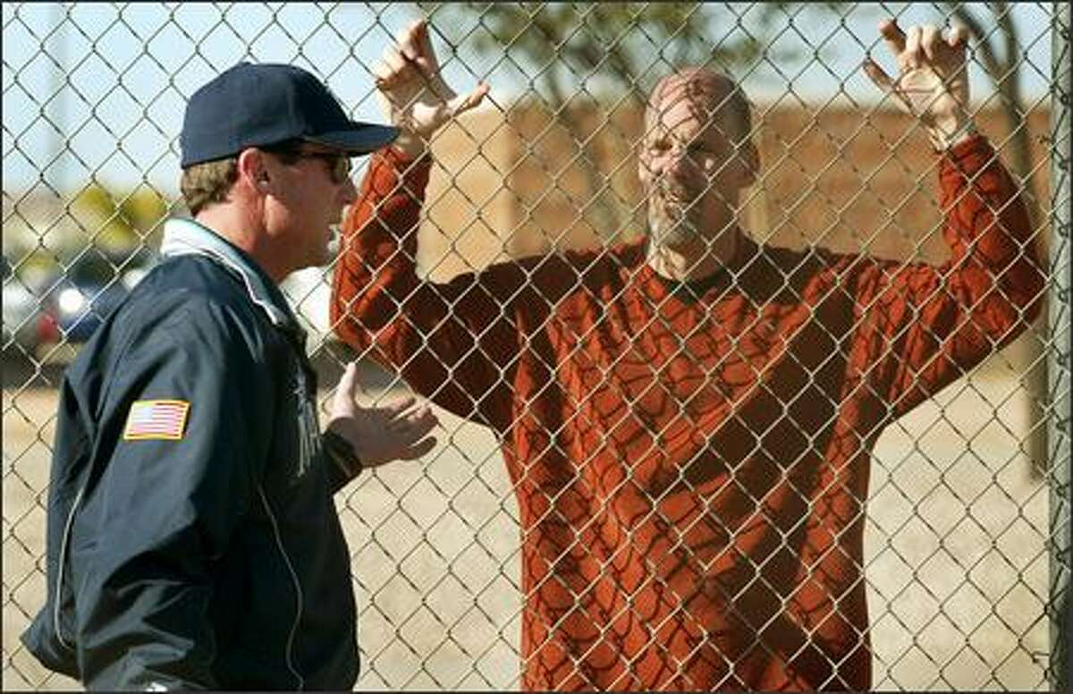 Mariners general manager Bill Bavasi, on far side of fence, talks with skipper Bob Melvin during spring training in Peoria, Ariz.